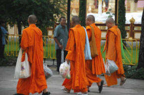Group of Thai monks gathering gifts from merit making